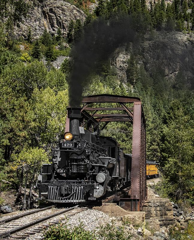 A - Open Maker: Brian Narveson  -- 34 points  2nd PlaceJudge's comments: Great smoke; lots of detail in the black engine; yellow cars gives depth; very sharpMaker's comments: This image was shot on the Durango and Silverton Railroad near Durango, Colorado.  Since the train was moving I shot in Shutter Priority set to 1/1000 second.   I set ISO at 800 to get an aperture setting of f/5.6 for depth of field.  Shot in full sun with a tripod and edited in Lightroom