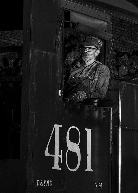 A - Prints Black and white printsMaker: Brian Narveson  -- 35 points  2nd PlaceJudge's comments: Engineer pops out from the darker areas; tells a story; very sharp; much detail in the blackMaker's comments: This image was shot at night in the roundhouse yard of the Durango and Silverton RR in Durango, Colorado. Zoom lens set to 95mm.  Camera mounted on tripod.  Aperture Priority was set to F/16 to star some bright lights that did not end up in the this cropped version.  Resulting shutter speed was 1 sec at ISO-1600.  Engine was not moving, which made the shoot possible.  Several blurry shots resulted for engineer moving.  Got lucky on this one.  Natural B&W photo as there was minimal color in the scene.