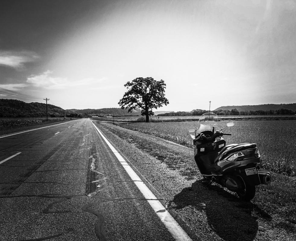 Maker: Daniel McKenzie  -- 26 points      Judge's comments: Very nice in B&W; good depth of field; might crop out some sky to put horizon in the third; image needs details in the motorcycle shadows; vignette seems too strongMaker's comments: iPhone 8+, taken in Houston County MN.
