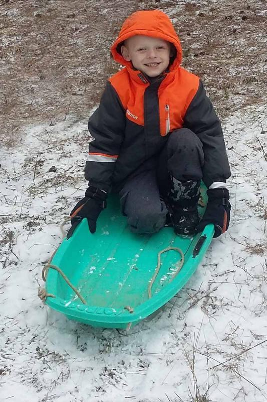 Maker: Lisa Gray  -- 28 points      Judge's comments: Fun winter photo; colors pop; great expression; eye goes to the empty part of the sled rather than child because he is so high in the frame; could shoot more from child's levelMaker's comments: